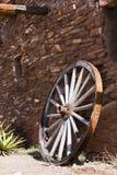 Gammalt hjul nära en stenvägg royaltyfri foto