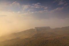 Gammalt hus överst av ett berg i molnen Arkivbilder