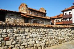Gammalt hus för sten med ett belagt med tegel tak och ett stort stenstaket i Bulgarien fotografering för bildbyråer