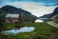 Gammalt hus i den norska sjön och dramatisk himmel arkivbild