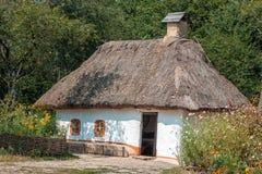 Gammalt hus med ett halmtäckt tak i byn Royaltyfria Bilder