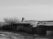 Gammalt hus på gatan nära tblack och vit arkivfoton