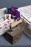 Gammalt järn som värmas av varma kol Lokaliserat på grått tyg Närliggande är vide- korgar, en bukett av torkade blommor och ett h fotografering för bildbyråer
