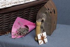 Gammalt järn som värmas av varma kol Lokaliserat på grått tyg Närliggande är vide- korgar, en bukett av torkade blommor och ett h arkivbild