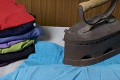 Gammalt järn som värmas av varma kol Lokaliserat på linnetyg Stå på en strykbräda Bredvid en bunt av klädde av skjortor royaltyfria bilder