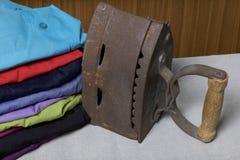 Gammalt järn som värmas av varma kol Lokaliserat på linnetyg Stå på en strykbräda Bredvid en bunt av klädde av skjortor royaltyfria foton