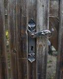 Gammalt järnhandtag i den wood dörren Royaltyfria Bilder