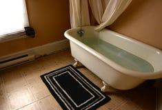 Gammalt jordluckrarefotbadkar i gammalt badrum arkivbild