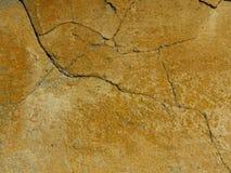 Gammalt knäckte den konkreta cementväggen som målades i guling fotografering för bildbyråer