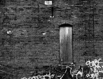 Gammalt komma med väggen med den dolda upp dörren och grafitti royaltyfria bilder