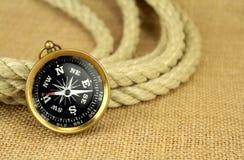 Gammalt kompass och rep på burlap royaltyfria foton