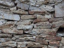 Gammalt kritisera stenväggen - bakgrundstextur Arkivfoton