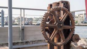Gammalt kugghjul för metall i port fotografering för bildbyråer
