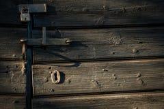 Gammalt lås på ladugårddörr i eftermiddagljus arkivbild