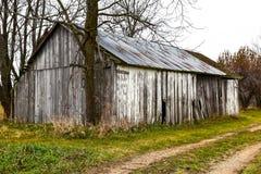 Gammalt ladugård eller skjul med ridit ut trä på lantgård Arkivbild