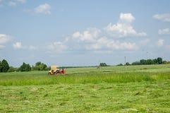 Gammalt landskap för land för dag för sommar för traktorsnittgräs Arkivbild