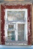 Gammalt lantligt fönster med sprucken målarfärg Arkivbild