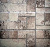 Gammalt lantligt golv med åldriga stentegelplattor av olika geometriskt ordnade format royaltyfri bild