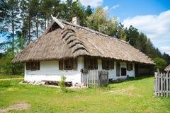 Gammalt lantligt hus med det halmtäckte taket Fotografering för Bildbyråer
