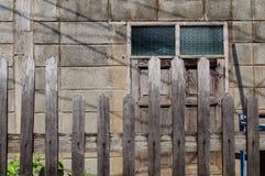 Gammalt lantligt hus med fönstret och trästaketet Arkivfoto