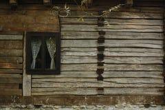 Gammalt lantligt trähus med ett fönster med vita virkade gardiner royaltyfri bild