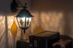 Gammalt latern på en vägg och resväskor fotografering för bildbyråer