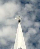 Gammalt mässingsfåfängt för väder överst av ett vitt konformat torn Arkivfoto