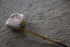 Gammalt mäta band på cementgolv arkivbilder