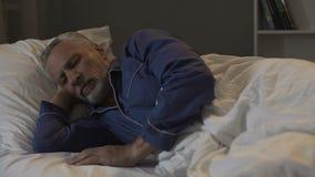 Gammalt manligt ligga i hans säng och sova, återställningstid och sund sömn, natt royaltyfria foton