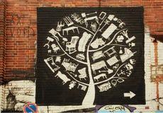 Gammalt möblemang på grafittikonstverk av tegelstenhemväggen Fotografering för Bildbyråer
