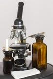 Gammalt mikroskop och två mörka flaskor arkivfoton