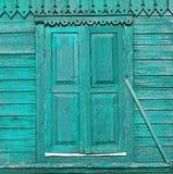 Gammalt målat grönt trästängt med fönsterluckor fönster på den dekorerade väggen Arkivbilder