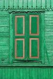 Gammalt målat grönt trästängt med fönsterluckor fönster på den dekorerade väggen Arkivfoton