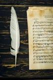 Gammalt musikark och en vingpenna Arkivbild