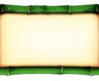 Gammalt nedfläckat papper mellan två bambupinnar royaltyfri bild