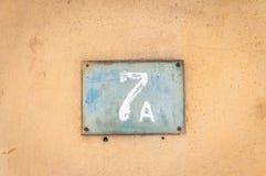 Gammalt nummer för platta för metall för tappninghusadress 7 A sju på murbrukfasaden av den övergav yttre väggen för hem på gatas royaltyfri bild