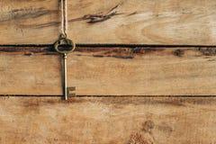 Gammalt nyckel- hänga på brunt trä Royaltyfri Foto