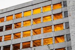 Gammalt oavslutat övergett för konkret byggnad, strålar av ljus till och med fönstren royaltyfria foton