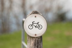 Gammalt och blekt inget cykeltecken på en träpelare i natur Arkivfoton