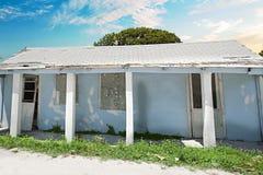 Gammalt och brutet hus med träd under den blåa himlen royaltyfria foton