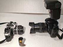 Gammalt och ny teknik för kamera handbokfilmkamera 1980 lins och speedlight för kontra 2002 DSLR AI arkivbild