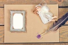 Gammalt papper, fjäder, ängel, ram på tabellen arkivfoton