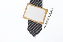 Gammalt pappers- kort på slipsen med den nya silverpennan på vit bakgrund Arkivbilder