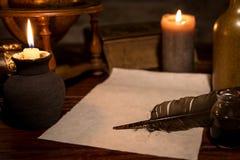 Gammalt pergamentpapper med en vingpenna och ett färgpulver, medeltida tema Royaltyfri Foto
