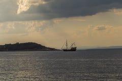 Gammalt piratkopiera träskeppet seglar i vattnet mot bakgrunden av solnedgången royaltyfri bild