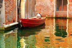 Gammalt rött fartyg nära de gamla byggnaderna i Venedig, Italien arkivbilder