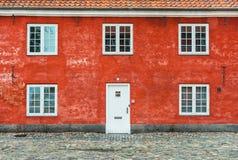 Gammalt rött hus med den vita fönster och dörren Royaltyfri Fotografi