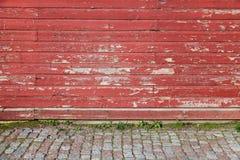 Gammalt rött trävägg- och kullerstengolv Arkivbilder