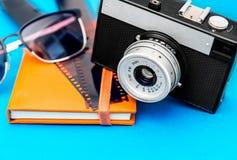 Gammalt retro kamera, filmremsa, solglasögon och fotoalbum på blått b Royaltyfri Bild