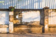Gammalt ridit ut lantligt betongvägg och staket längs trottoaren i f Arkivbilder